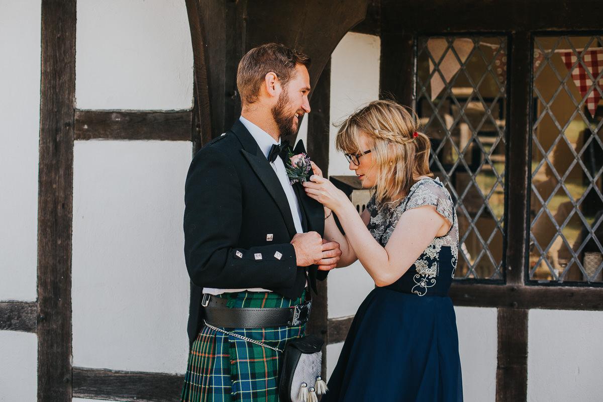 bridesmaid giving groomsmen buttonhole