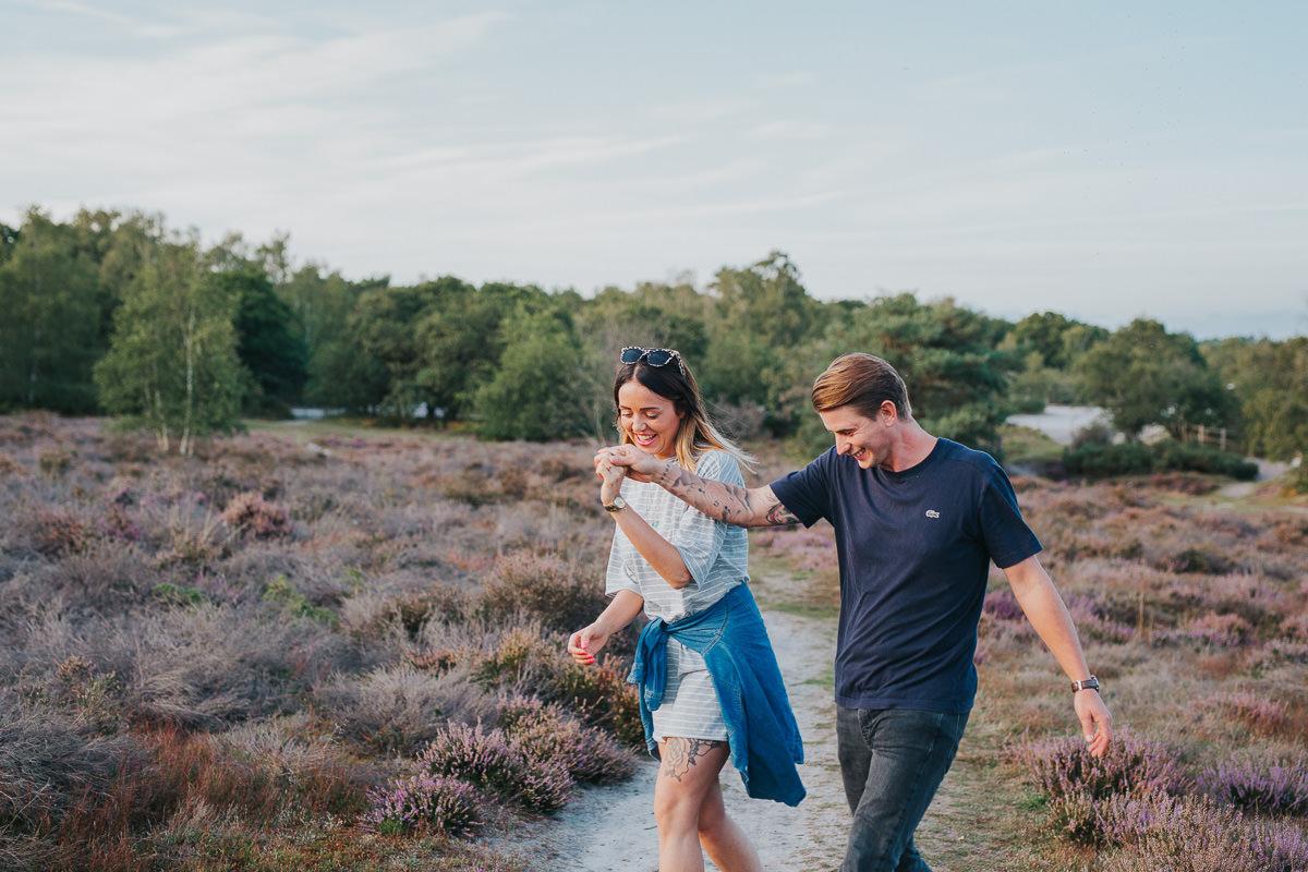 fun couple walking in field