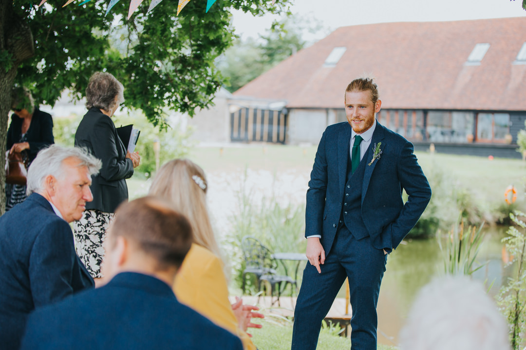 groom waiting for bride to arrive at outdoor ceremony